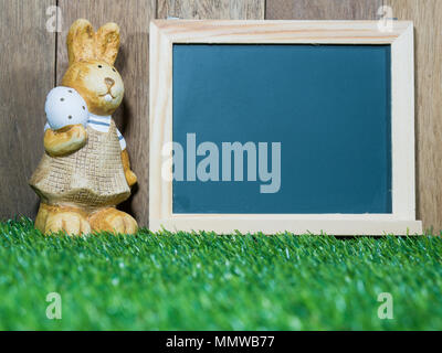 The easter rabbit stands beside the blackboard. Blackboard with easter rabbit placed on green grass. Easter day concept. copy space for text - Stock Photo