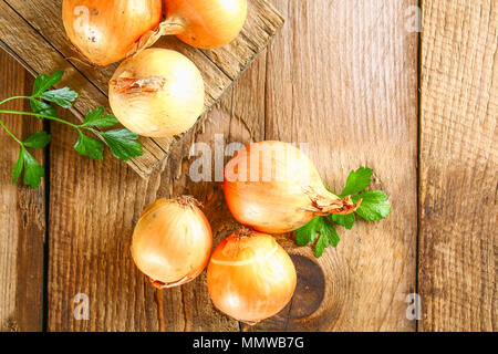 Yellow onion with parsley on a wooden table - Stock Photo
