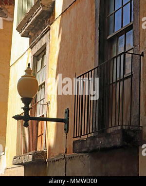 What looks like a old lamp, but could be a modern representation sits on a wall   on the Rue da Cadeia velha in Funchal on the island of Madeira - Stock Photo