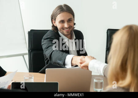 Smiling businessman in suit handshaking female partner at group  - Stock Photo