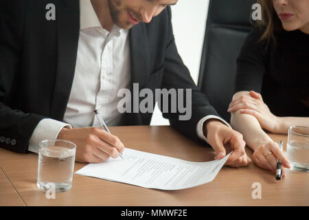 Satisfied smiling businessman in suit signing contract at meetin - Stock Photo
