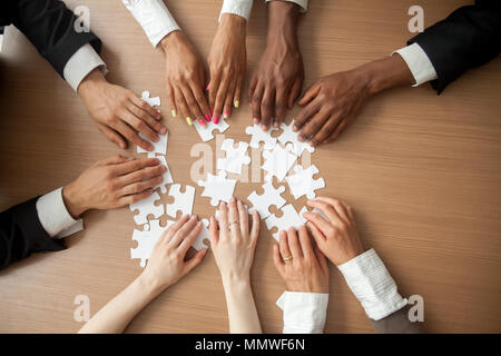 Hands of diverse people connecting puzzle together, top closeup  - Stock Photo