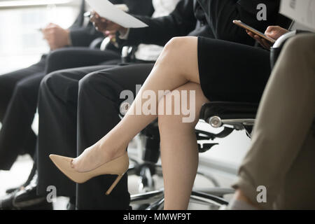 Business people sitting in row waiting for interview, legs close - Stock Photo