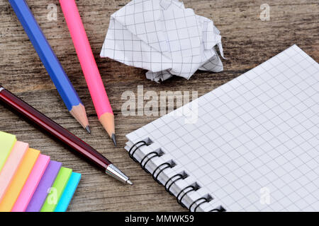 Empty notepad with pencils anc colorful notes on wooden table - Stock Photo