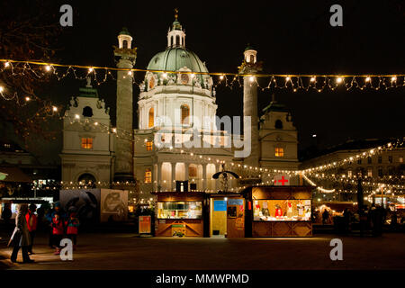 evening atChristmas market in front of Vienna's Karlskirche with festive lighting, stalls and the illuminated baroque church in the background - Stock Photo
