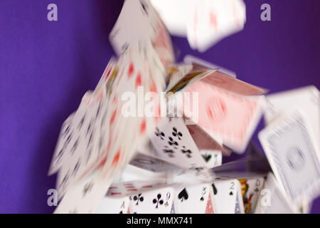 A house of playing cards collapsing - a metaphor for a complicated organisation or plan that has gone wrong - Stock Photo
