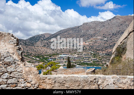 Panoramic view from the ruined walls of Spinalonga (Kalydon) fortress to Plaka village, Crete. Picturesque scene, arid, mediterranean landscape - Stock Photo