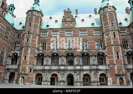 The inner courtyard, Frederiksborg  Castle, Hillerod, Denmark.  Red brick building, striking green towers and a stormy sky background - Stock Photo