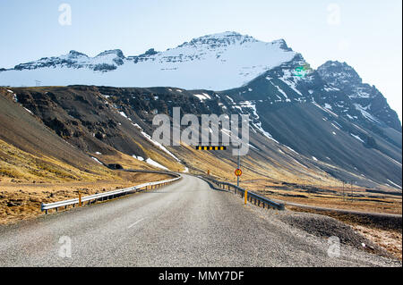 Route 1 (Ring Road) along the Eastern Fjords, Iceland. Colourful landscape, snowcapped mountains, grassy slopes and winding road - Stock Photo