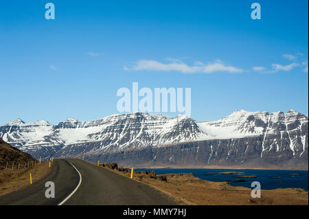 Spectacular scenery along the Eastern Fjords road near Seydisfjordur, Iceland. Stark contrast between the white, snow-capped peaks, blue water and sky - Stock Photo