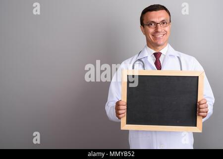 Man doctor wearing eyeglasses against gray background - Stock Photo
