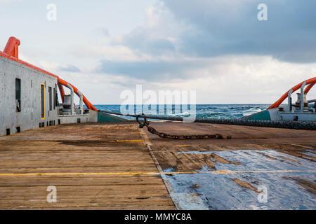 Anchor-handling Tug Supply AHTS vessel doing static tow tanker lifting. Ocean tug job. - Stock Photo