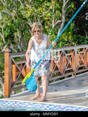 Antigua Lesser Antilles islands in the Caribbean West Indies - Woman on holiday cleaning infinity swimming pool - Stock Photo