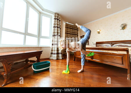 Woman cleans up the apartment, she washes floors and does a sports warm-up. - Stock Photo