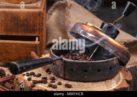 The device for roasting coffee beans, an old hand grinder. Smoky roast coffee on a wooden stand. Studio lighting. - Stock Photo