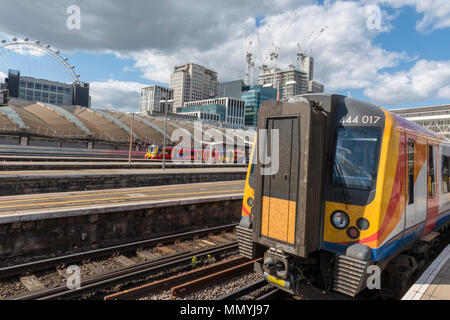 A south western railway train in a platform at london waterloo station with the london eye and new construction behind. Railways and trains commuting. - Stock Photo
