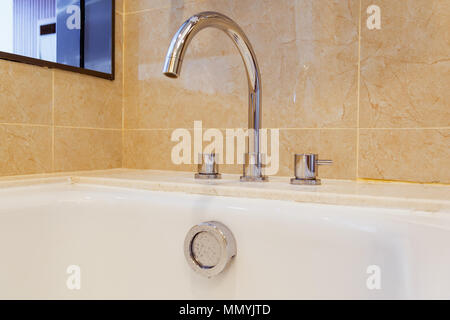 Tap and overflow button on bathroom - Stock Photo