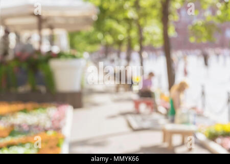 Unrecognizable silhouettes of people walking in the city street and resting on the benches at sunny day. Urban modern abstract background. Blurred effect - Stock Photo