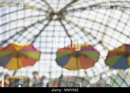 Unrecognizable people resting sitting in cafes under bright umbrellas at sunny day with transparent roof. Urban modern abstract background. Blurred effect. Copy space - Stock Photo