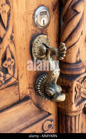 Brass door knocker on a hand carved wooden door in San Miguel de Allende, Mexico - Stock Photo