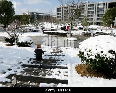 Small child enjoying the snow in Shanghai - Stock Photo