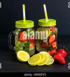 Mojito cocktail with lime slices and strawberries and mint in a jar on a dark wooden background. Summer non-alcoholic drink - Stock Photo