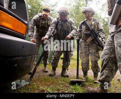 U.S. Air Force Staff Sgt. Edgar Cerrillo, left, 435th Security Forces Squadron Ground Combat Readiness Training Center instructor, instructs Contingency Response Top-Off course participants with the 435th Contingency Response Group on how to check a vehicle for explosives at Rhine Ordinance Barracks, Germany, Aug. 3, 2017. During the course, 21 participants acquired skills designed to help them augment the 435th SFS, while carrying out the 435th CRG mission of opening up bare bases and airfields in austere environments. (U.S. Air Force photo by Senior Airman Elizabeth Baker) - Stock Photo