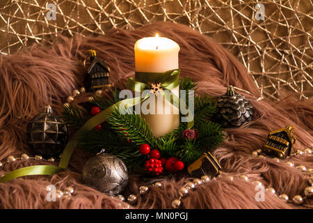 New Year's still life with a burning candle, a Christmas decorations and pine branches