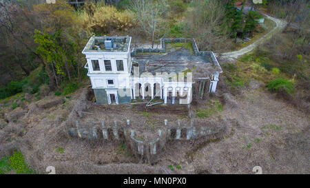 Drone view of abandoned building of classical architecture with dense thickets of dry ivy, Sochi, Russia - Stock Photo