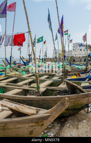 Cape Coast, Ghana - February 15, 2014: Colorful moored wooden fishing boats in African harbor town Cape Coast with colonial castle in background - Stock Photo