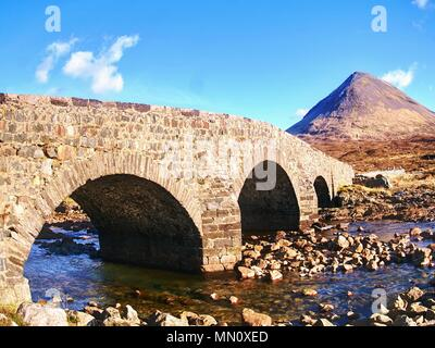On the way to Scottish Highlands Springtime. Old vintage stony bridge crossing river in Sligachan, scottish landscape - Stock Photo