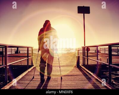 Hurt man with hooded jacket and forearm crutches  standing on sea bridge within  early morning and thinking. Gloomy nostalgic silhouette of sad lonely - Stock Photo