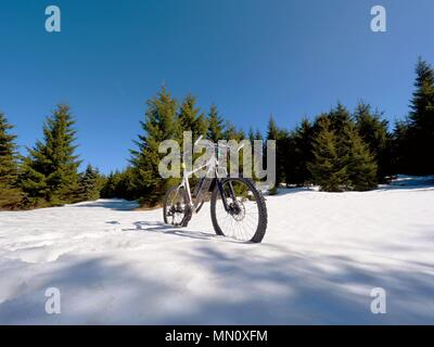 Close wide view to mountain bike stays in snow. Winter snowy mountains with road between trees. - Stock Photo
