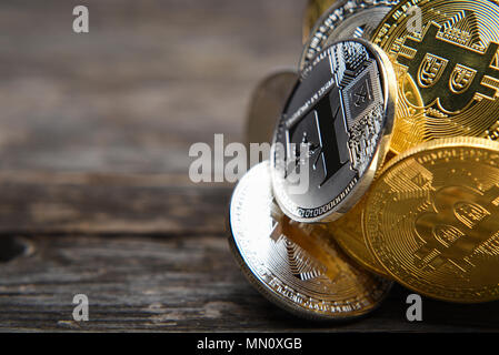 Group of golden and silver Bitcoin Ethereum Litecoin on wooden surface, macro with copy space for text, business concept - Stock Photo