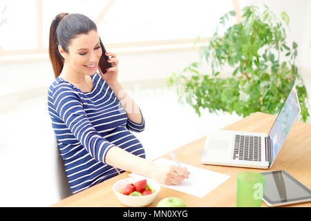 High angle shot of pregnant woman making call and writing something while sitting behind laptop at desk. Home office. - Stock Photo