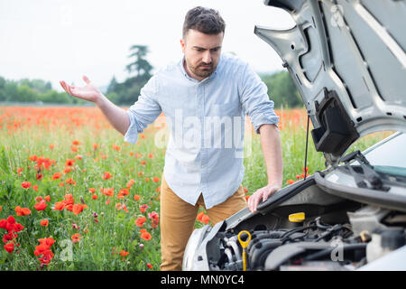 Young man waiting the car tow service after a vehicle breakdown - Stock Photo