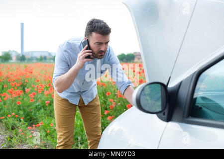 Caucasian man stand front a broken car calling for assistance - Stock Photo