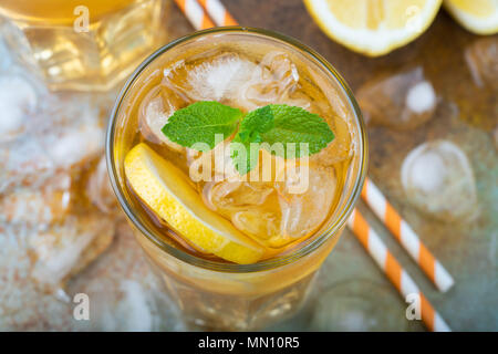 Traditional iced tea with lemon, mint and ice in tall glasses. A glass of refreshing summer drink on the old rusty background. Top view - Stock Photo