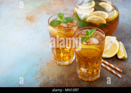 Traditional iced tea with lemon, mint and ice in tall glasses. Two glasses with cool summer drink on old rusty background. With copy space - Stock Photo