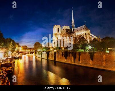 Nighttime comes over Notre Dame along the River Seine.  Paris, France.