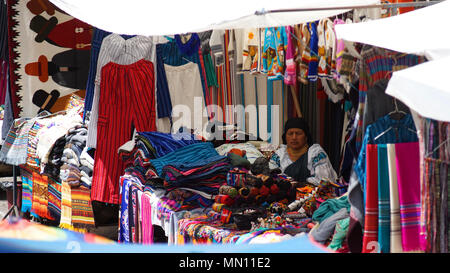 Indigenous woman sitting selling her weavings and crafts in the Plaza de los Ponchos - Stock Photo