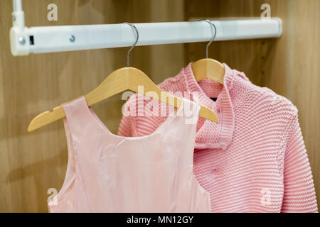 A row of children clothes hanging on hangers. Fashion for girls.Wardrobe with kid clothes.wooden Hangers with pink clothes. Set for girl - Stock Photo
