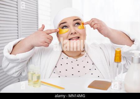 Pretty fat woman making an eye mask - Stock Photo