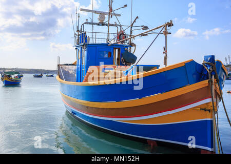 Traditional colorful fishing boat, luzzu, anchored at Marsaxlokk, the historic port of Malta. Blue sky with clouds and village background. Close up vi - Stock Photo