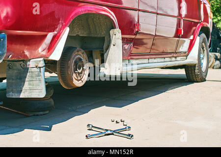 Changing a wheel or tire on an old vintage red van at outdoor car service - Stock Photo