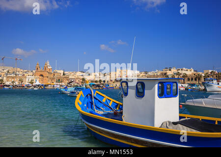 Traditional colorful fishing boats, luzzu, anchored at Marsaxlokk, the historic port of Malta. Blue sky and village background. Close up view. - Stock Photo