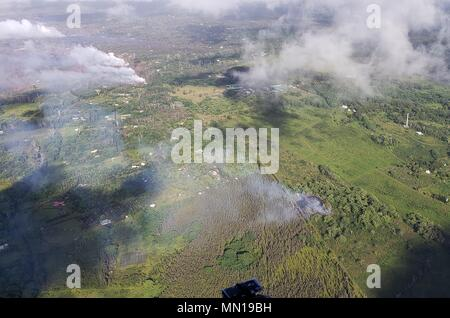Hawaii, USA 12th May 2018. An aerial view of steam and lava escaping from newly formed fissure 16 from the Kilauea volcano May 12, 2018 in Leilani Estates, Hawaii. The fissure is located 500 meters northeast of the Puna Geothermal Venture site (top right). Credit: Planetpix/Alamy Live News - Stock Photo