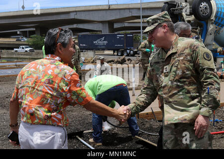 Honolulu, HI – Hawaii National Guard Maj. Gen. Arthur J. Logan greets Duane Kurisu at the Kahauiki Village Homeless Relocation Project, Aug. 9, 2017 in Honolulu, Hawaii. Soldiers continued to prepare foundation slabs for future affordable housing for homeless families. (U.S. Army National Guard photo by Spc. Matthew A. Foster) - Stock Photo