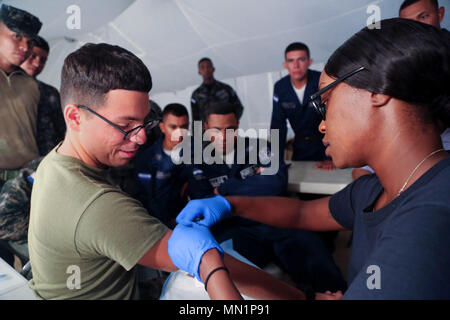 170809-A-QE286-0300 PUERTO CASTILLA, Honduras (August 9, 2017) U.S. Navy Hospital Corpsman 1st Class Petty Officer Kara Irons, the command tactical combat casualty care program manager at Naval Health Clinic Quantico, prepares to take a blood sample from Lance Cpl. Marcus Salazar, assigned to the 8th Engineer Support Battalion, as Honduran troops look on, during a combat lifesaver course, in support of Southern Partnership Station 17. SPS-EPF 17 is an annual series of U.S. Navy deployments focused on subject matter expert exchanges with partner nation militaries and security forces in Central  - Stock Photo