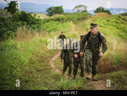 U.S. Marine Corps Sgt. Jeremy Pogue, a rifleman with 1st Battalion, 1st Marine Regiment, 1st Marine Division, hikes to Gunnery Sgt. John Basilone's fighting hole during a tour of Bloody Ridge in Guadalcanal, Solomon Islands, Aug. 9, 2017. The tour was used to teach the Marines about Bloody Ridge and the Battle of Guadalcanal, which took place from Aug. 7, 1942 to Feb. 9, 1943. (U.S. Marine Corps photo by Sgt. Wesley Timm) - Stock Photo